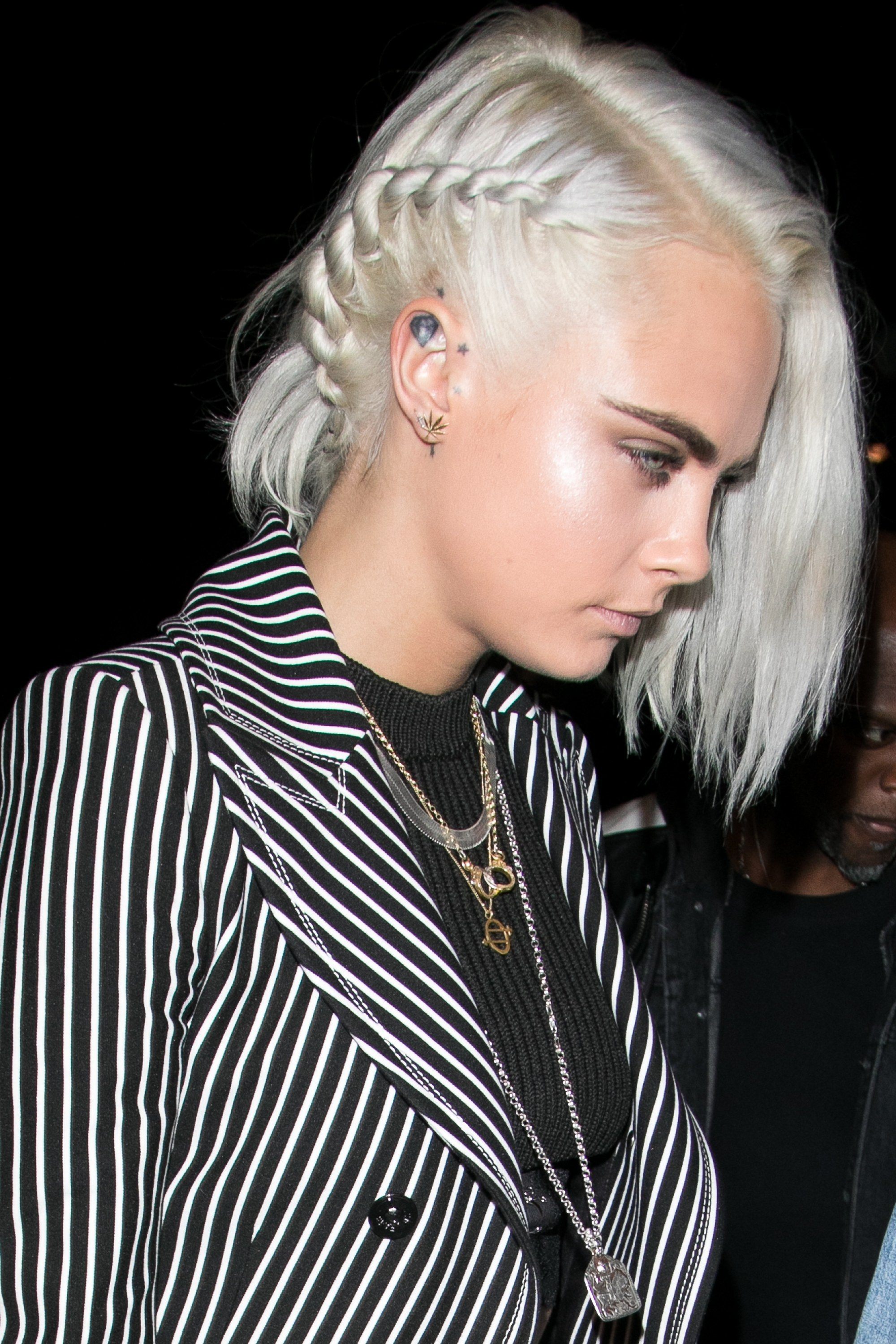 cara delevigne with platinum blonde, shoulder length bob, side-parted and braided on one side, wearing a black and white striped blazer, and black top