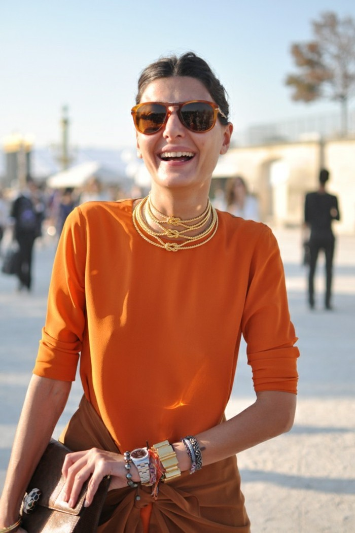 business casual women, smiling brunette with sunglasses, wearing plain bright orange top, with three knotted pearl necklaces, wristwatch and many different bracelets