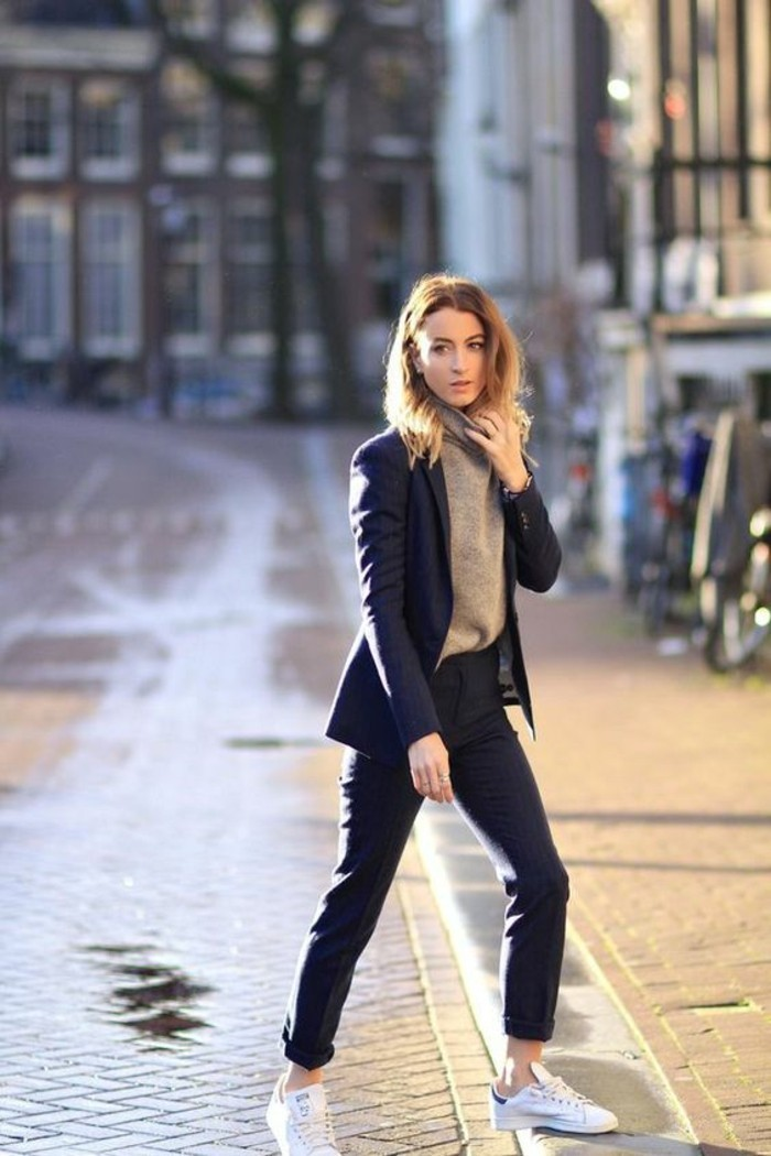 business casual women, woman with messy blonde hair, wearing dark grey trousers with rolled up ankles, with beige turtleneck top, white sneakers, and dark blue blazer