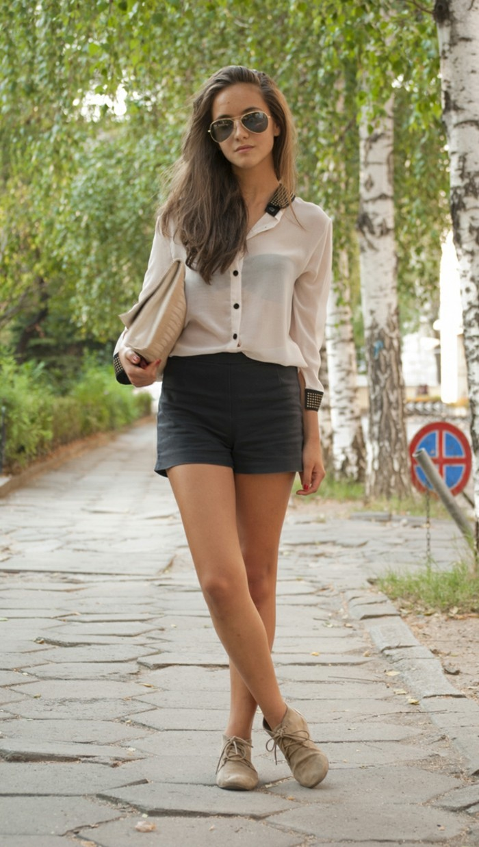 casual business attire, dark shorts and pale beige lace-up shoes, worn with pale pink shirt with black buttons and details, by brunette woman with sunglasses, holding cream leather clutch