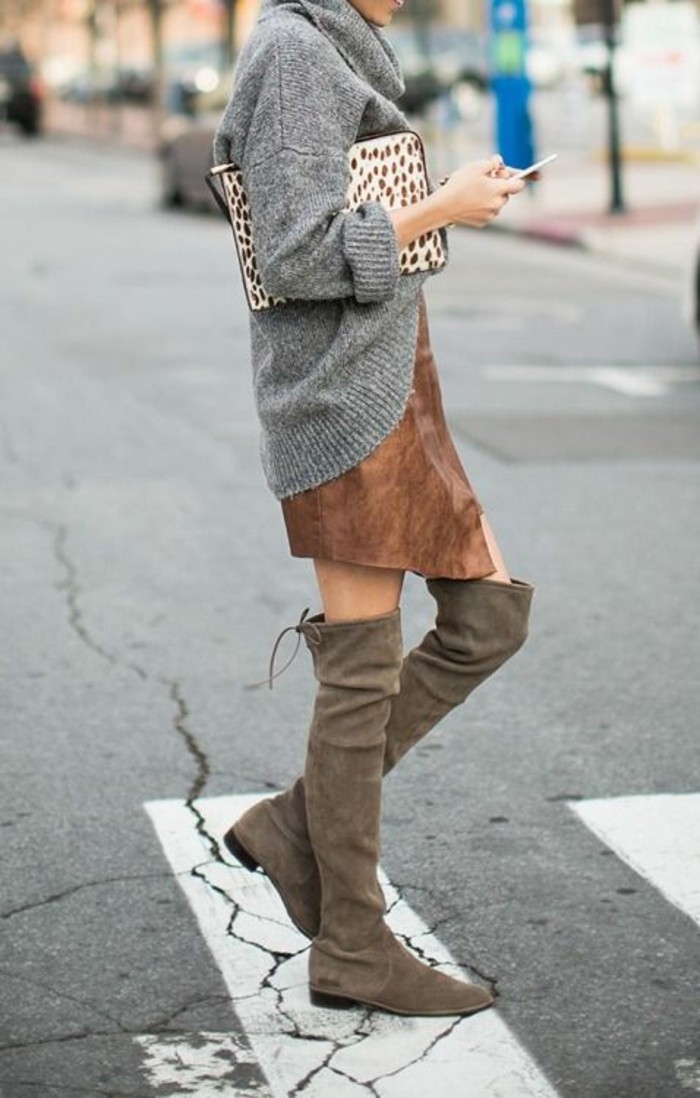 business casual for young women, grey oversized turtleneck jumper, over brown suede mini skirt, worn with beige over the knee boots, by woman holding large animal-print clutch