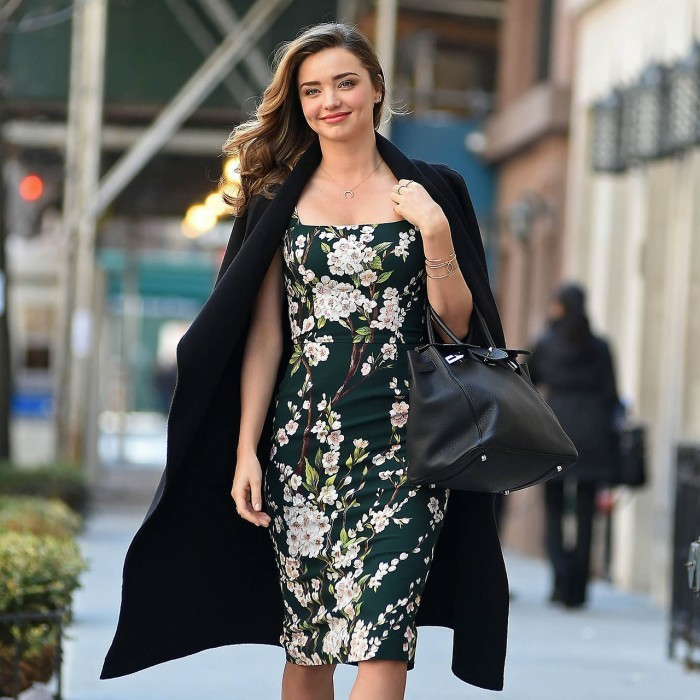 casual clothes, smiling miranda kerr, wearing a black coat over her shoulders, with dark green floral patterned dress, and black leather bag