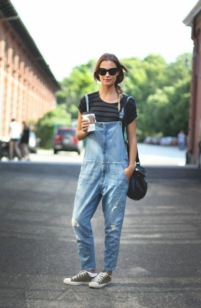 grey and black striped t-shirt, and baggy pale denim overalls, worn by brunette woman with braided hair, with sunglasses and black leather bag