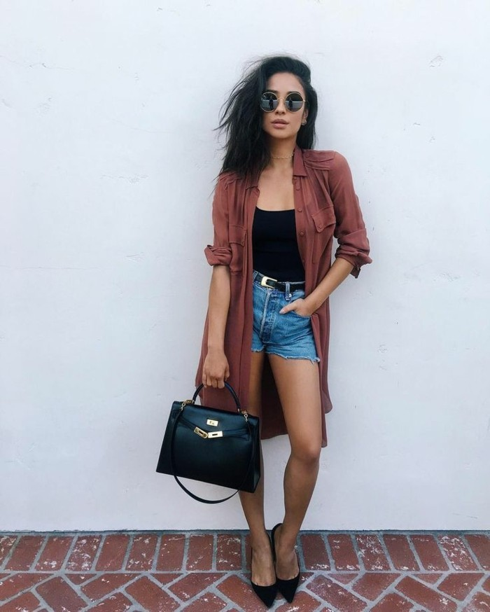 women outfits, black-haired woman with round sunglasses, wearing pale red oversized shirt with rolled sleeves, over black top and cut off denim shorts, with black belt, high heels and black leather bag