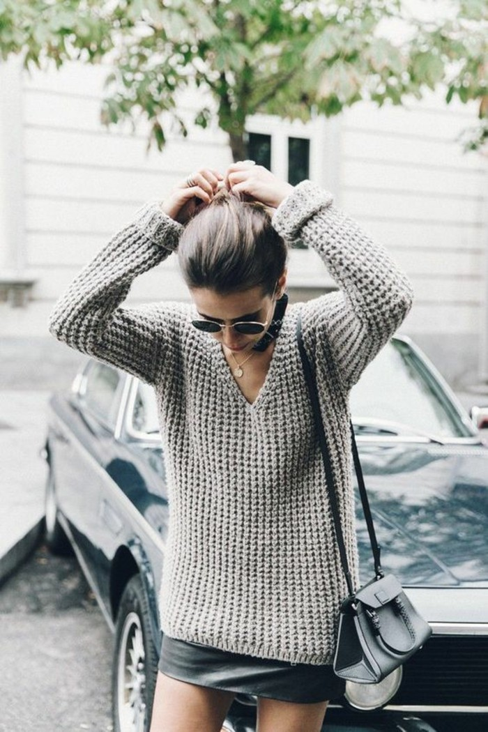 women outfits, long chunky knit, pale grey v-neck sweater, worn over black leather mini skirt, by brunette woman with sunglasses, and small leather shoulder bag