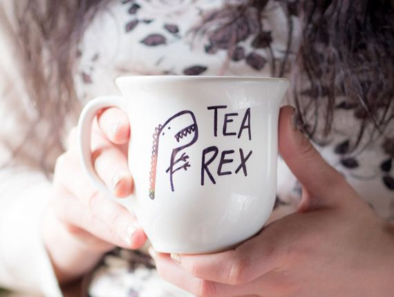 hands holding a whote ceramic mug, decorated with a simple doodle, fun and easy crafts, showing a dinosaur and the words tea rex