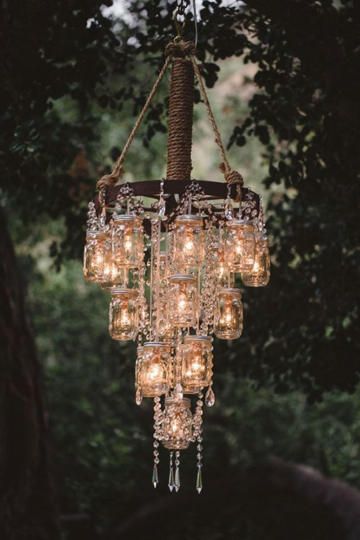 mason jar crafts, chandelier made of mason jars, containing lit fairy lights, with crystal decorations, hanging from a tree