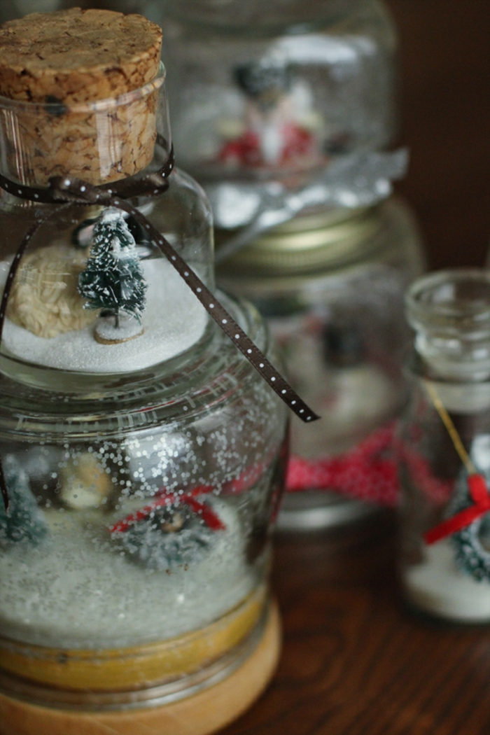 christmas mason jars, several jars transformed into snow globes, containing fake snow, and little christmas tree figurines
