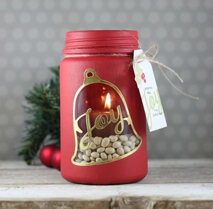 christmas mason jars, a jar painted in red, with a bell-shaped window, decorated with gold and the word joy, and revealing a lit candle, placed on a row of white beans