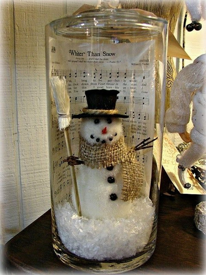 christmas mason jars, large clear jar, containing fake snow, a snowman figurine, and a sheet music page