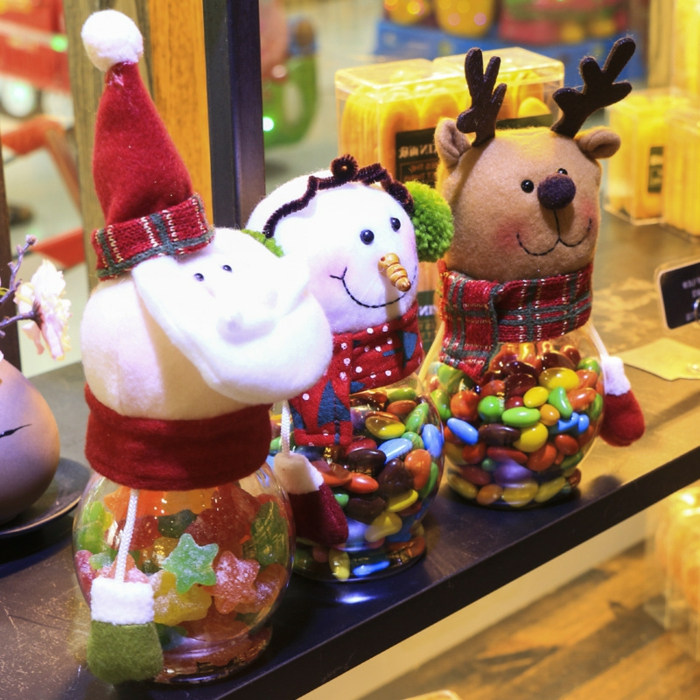mason jar crafts, three jars filled with multicolored candy, covered with plush heads of stanta, a snowman and a reindeer