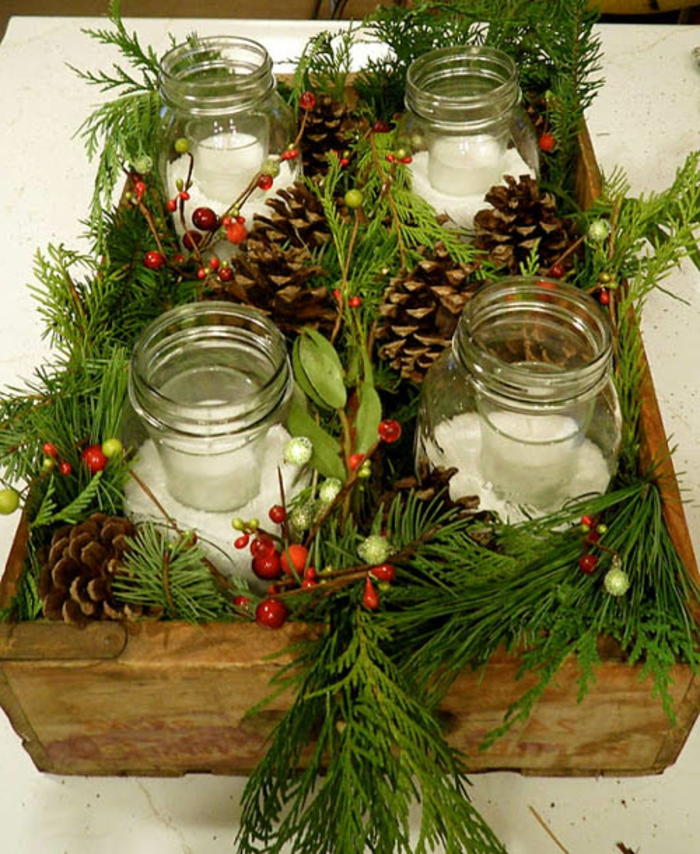 christmas mason jars, four jars containing fake snow, and small glasses with candles, placed in a wooden tray, next to fir branches, fir cones and berries, and other plants