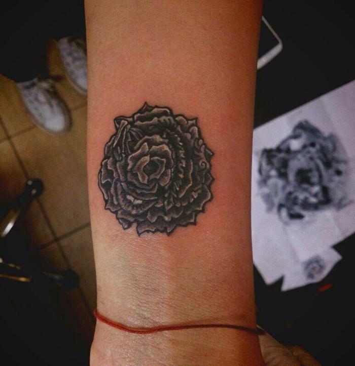 lotus flower tattoo, close up of unusual, dark floral tattoo, near a person's wrist