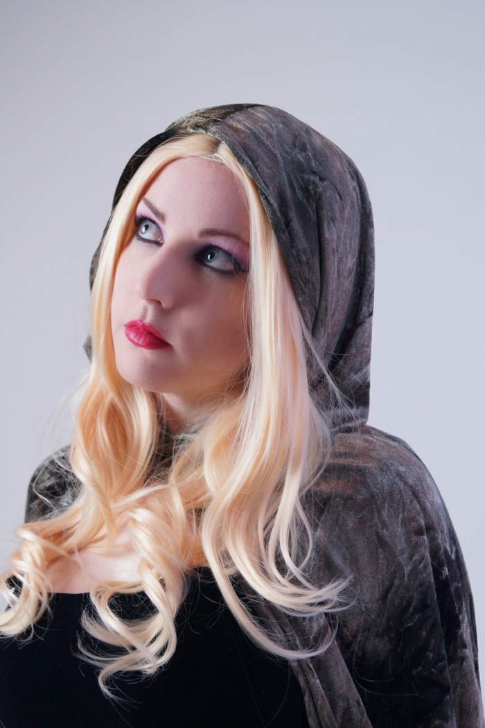 woman with red lipstick, black eye-make-up and blonde wig, wearing a black top, and dark grey velvet cape and hood, renaissance braided hairstyles