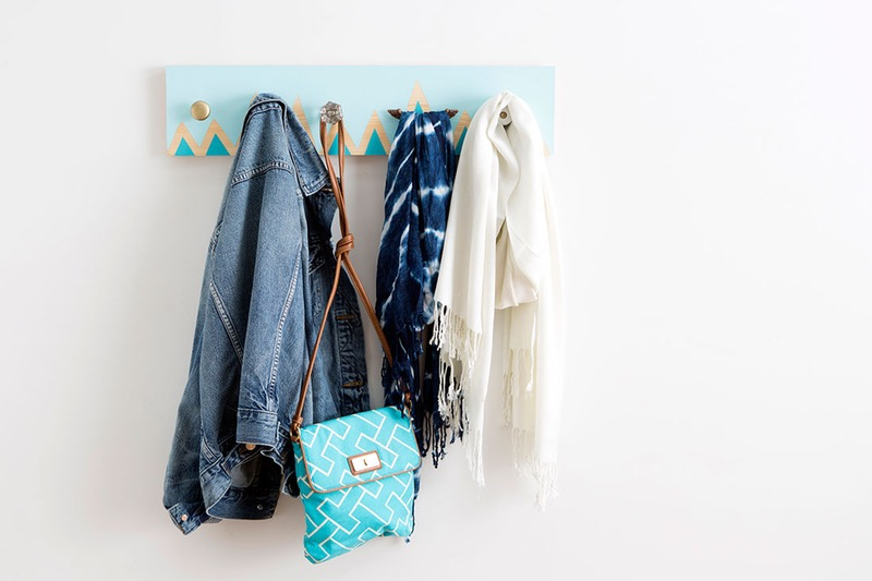 coat hanger made from wooden plank, painted pale blue, with yellow and dark blue pattern, denim jacket and blue bag, and two scarves hanging from it