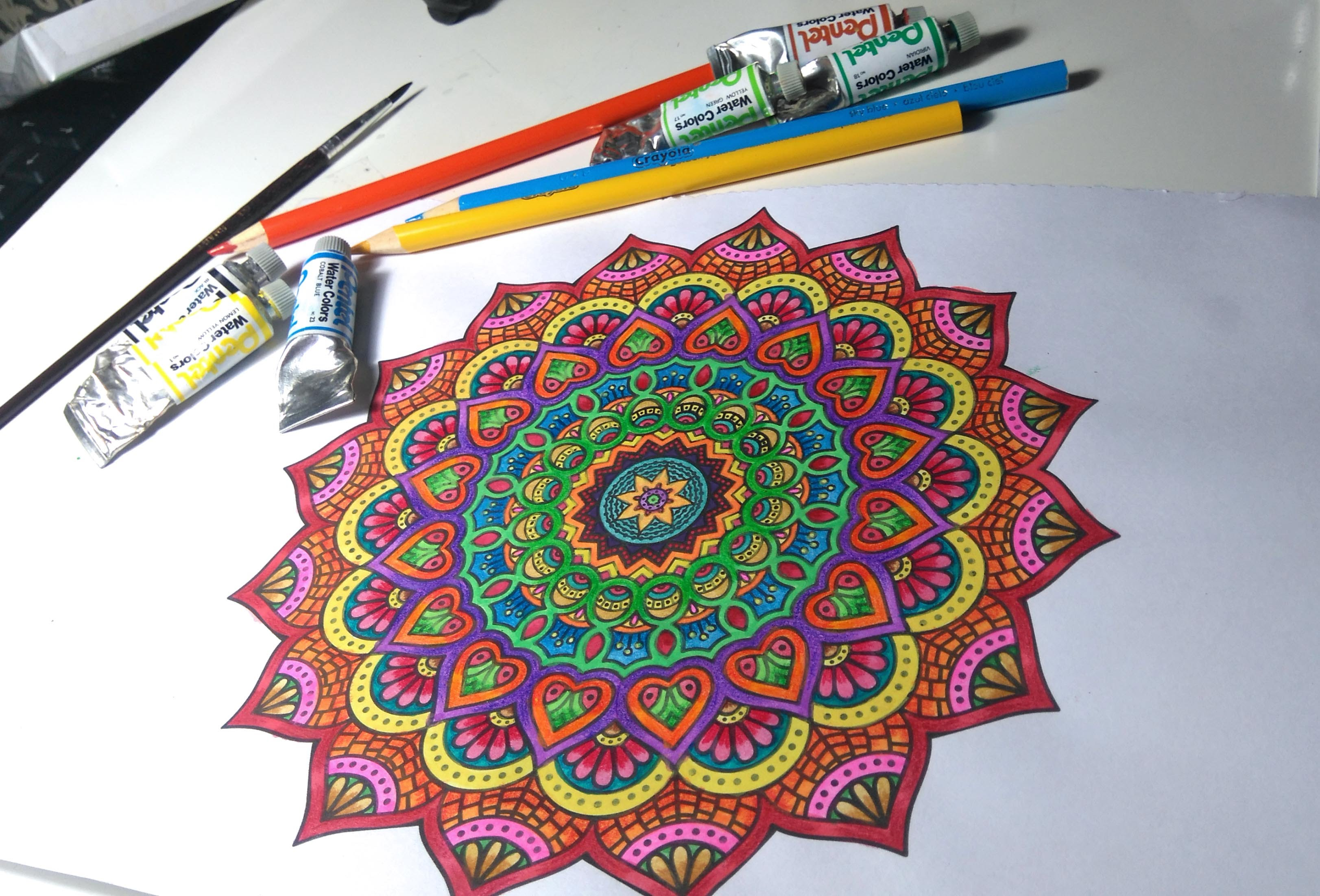 flower mandala in yellow, orange and red, pink and blue, craft ideas, colored pencils and tubs of paint in background
