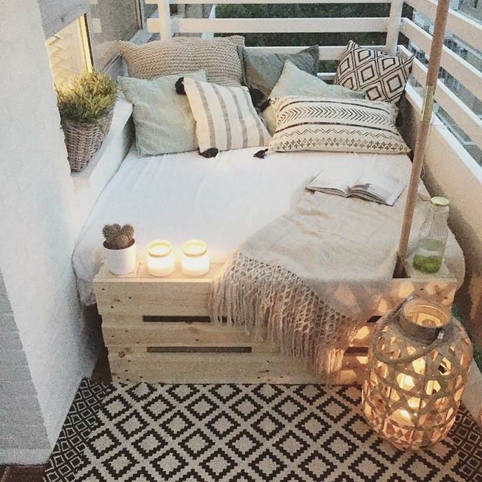 porch ideas, settee made from wooden pallets, with white cover, and many pale patterned cushions, several lit candles, potted plants and blanket