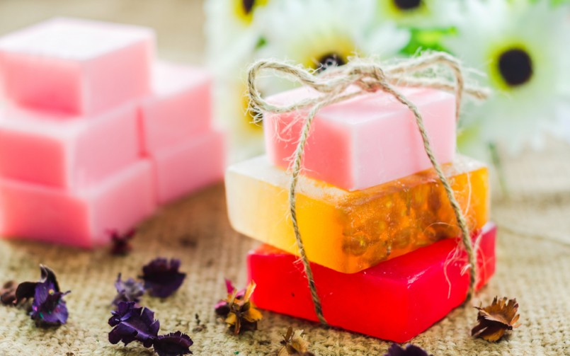 three handmade soaps, red orange and pink, stacked on top of each other, and tied with string, homemade crafts, more pink soaps in background