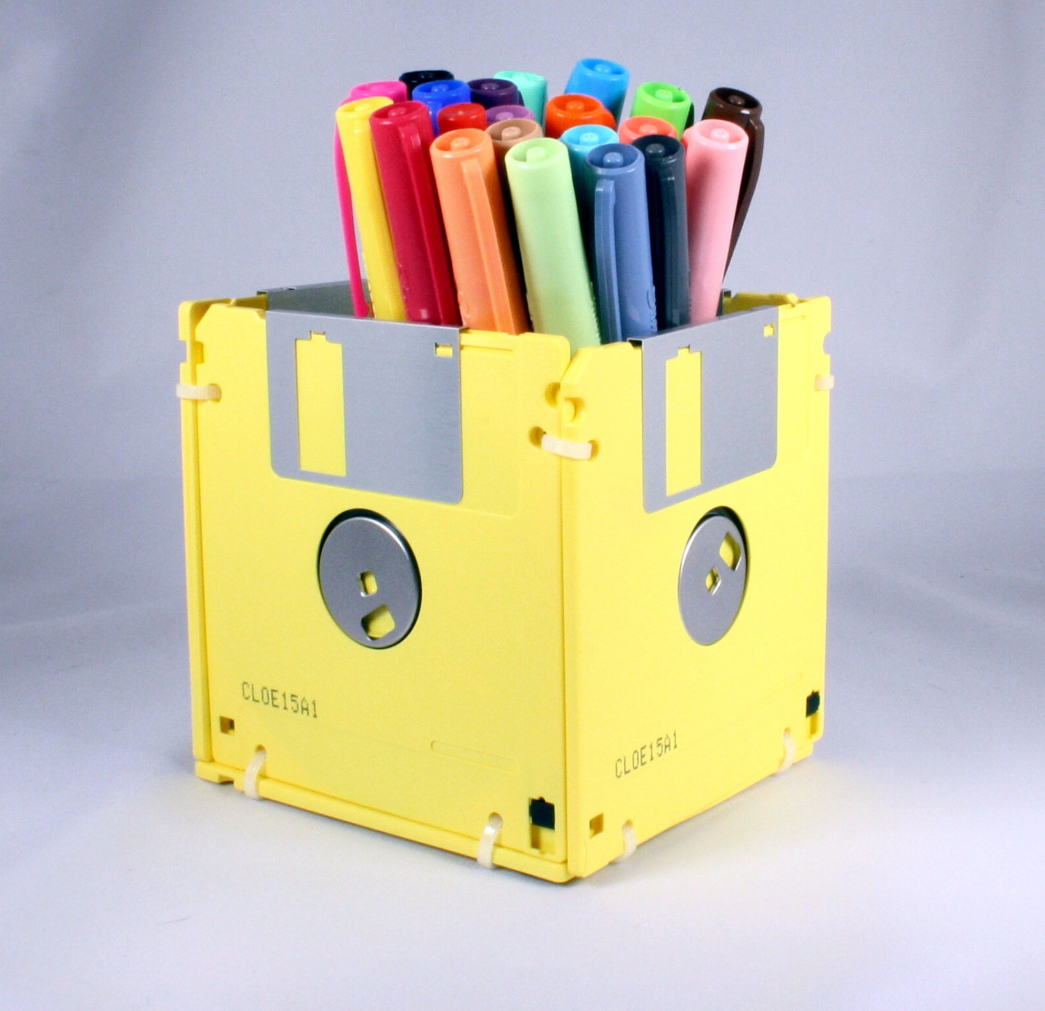 close up of a pencil case, made from several yellow floppy disks, art and craft ideas, markers or pens in different colors inside