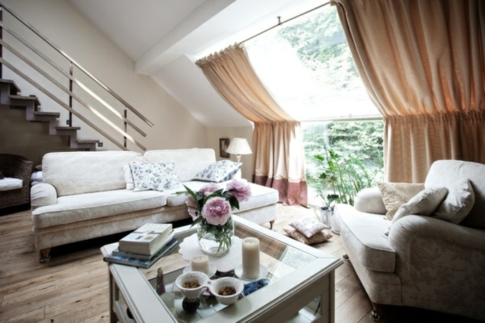 curtains for living room, light patterned sofa and settee, white glass-top table, wooden floor and staircase, big sloped window, with light brown curtains