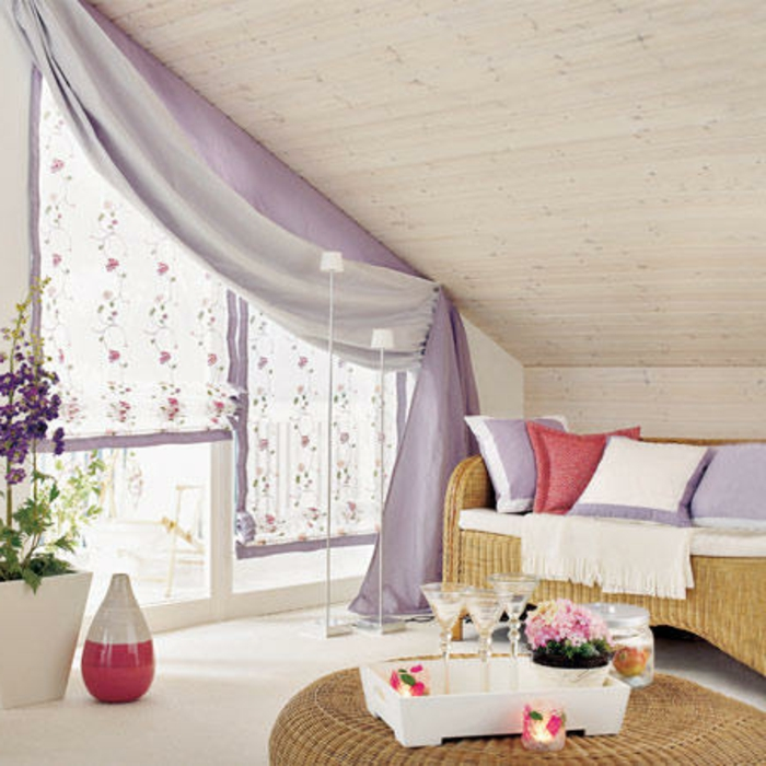 curtains for living room, wicker round table, and settee with cushions, large window with a combination of sheer white, and pale purple curtains