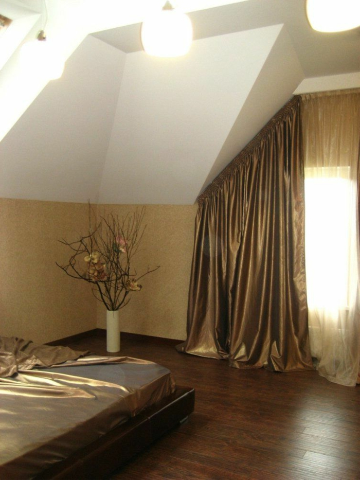 bedroom with white walls and cream paneling, bed with shiny, pale brown metallic cover, window with matching drapes, and sheer cream curtains