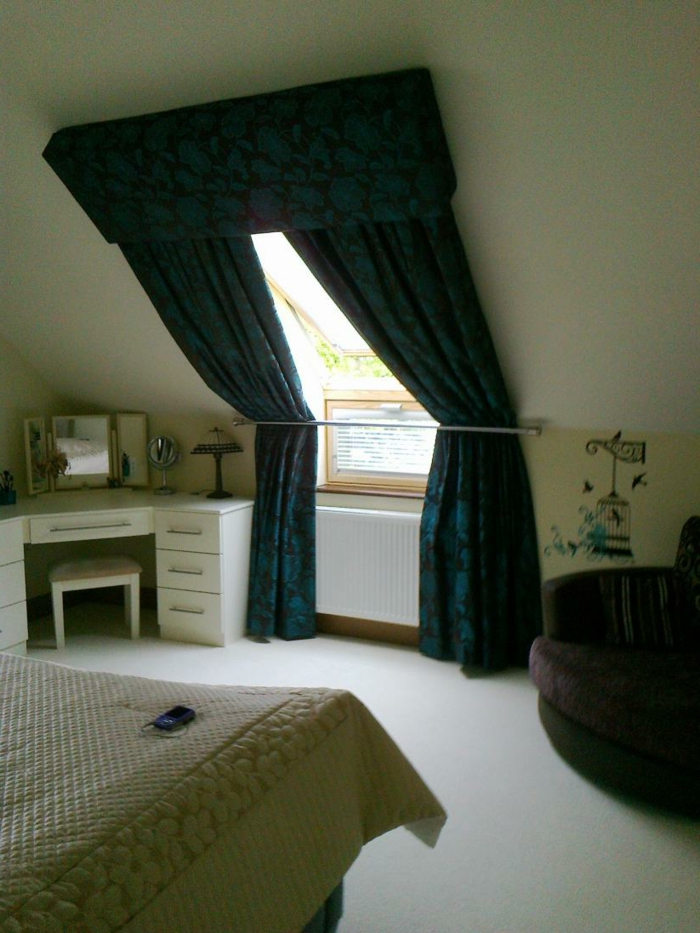 bedroom curtains, room with white vanity, bad with cream-colored patterned cover, brown settee and sloping window, with dark green and black patterned curtains, held with metal rod