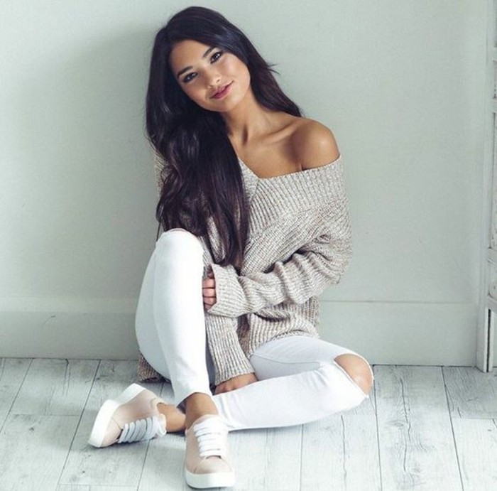 business casual for young women, chunky knit beige v-neck jumper, white torn skinny trousers, and pale pink and white sneakers, worn by smiling dark-haired woman