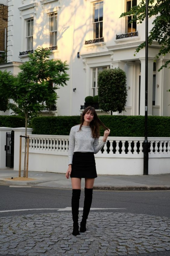 casual business attire, woman with long brunette hair and bangs, wearing pale grey sweater, black mini skirt, and black over the knee high-heeled boots