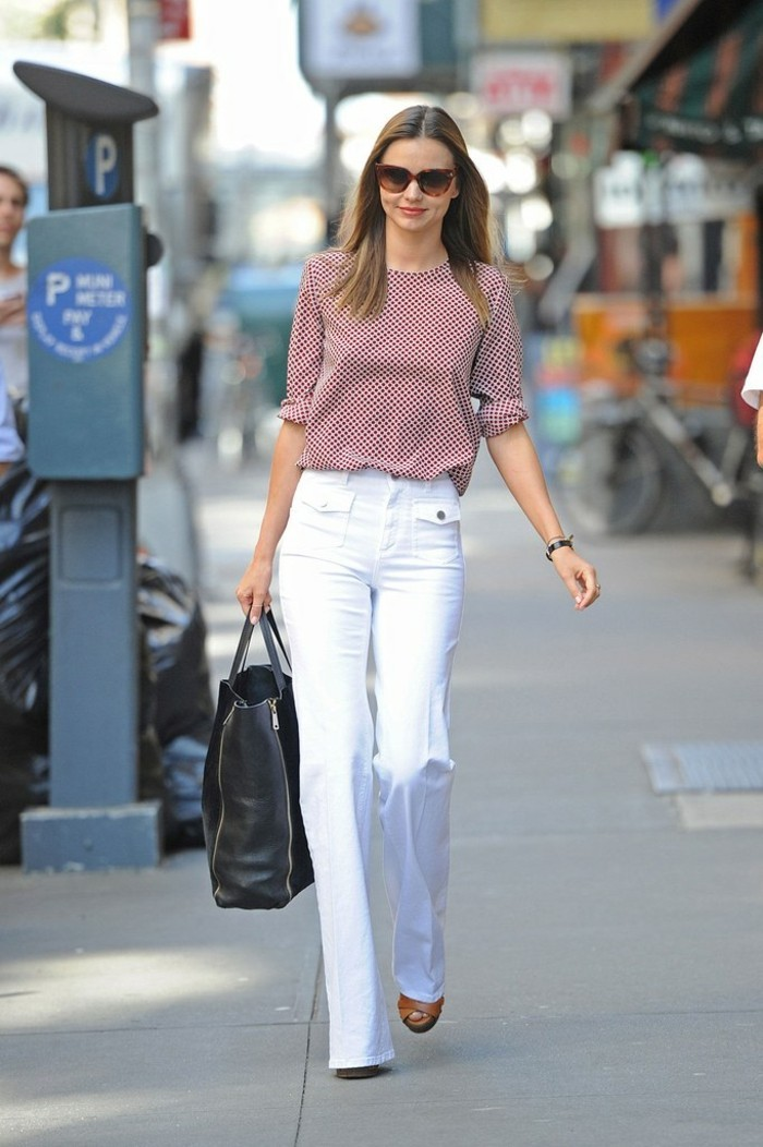 casual dress code, miranda kerr with sunglasses, wearing red and white patterned top, and white straight trousers, and holding large black leather bag