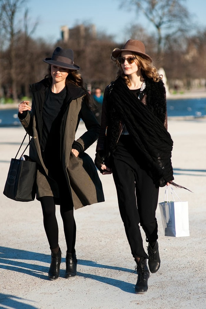 women business casual, woman in black outfit, with grey winter coat and black felt hat, walking next to woman in black trousers, with brown felt hat, and black scarf