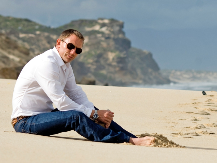 skinny business casual jeans, and white shirt, worn by daniel craig, with aviator sunglasses, sitting barefoot, on a sandy beach
