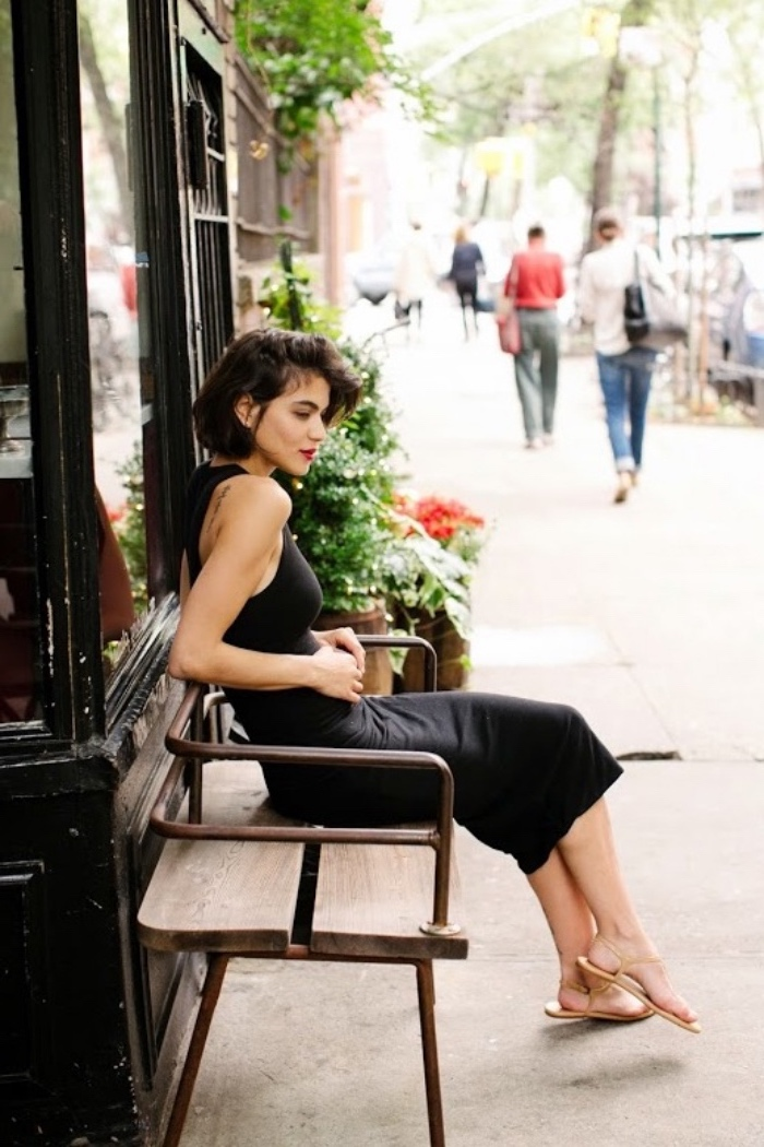 brunette woman with short bob haircut, wearing black midi dress, and beige sandals, and sitting on a bench