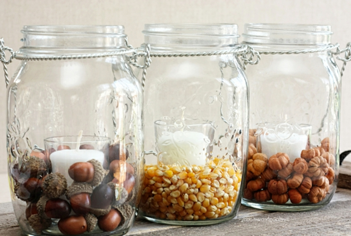 decorating mason jars, three jars with twisted wire handles, each containing a white candle in a glass, and either acorns, corn or micro pumpkins