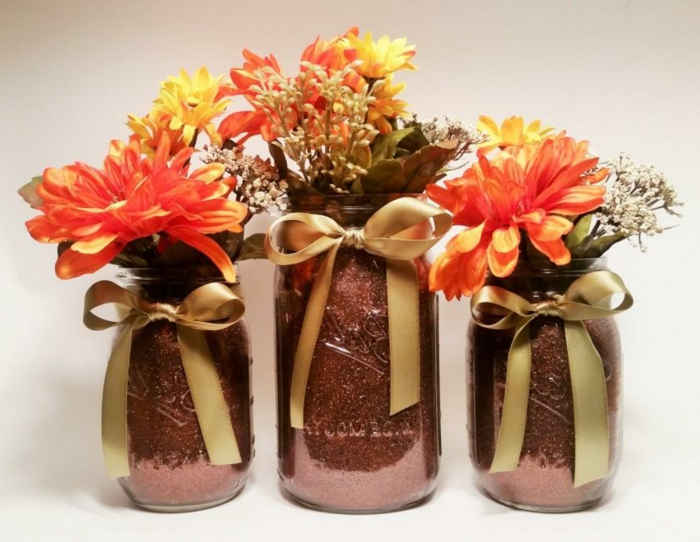 diy mason jar, three jars of different sizes, painted in a dark pink, glittery color, and decorated with gold bows, containing orange and yellow flowers