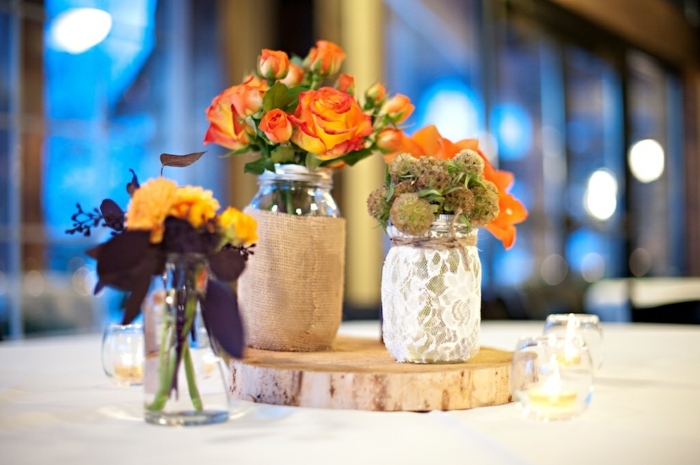 mason jar gifts, three jars either decorated with burlap, lace or kept plain, placed on a table, and containing various flowers in orange and yellow