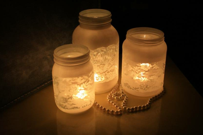 diy mason jar, three differently sized jars, painted white and featuring a lace pattern, lit from within and placed in a dark room, near a pearl necklace