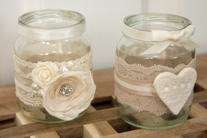 mason jar gifts, two small clear jars, with white lace, ribbons, faux flowers and a heart ornament stuck to them