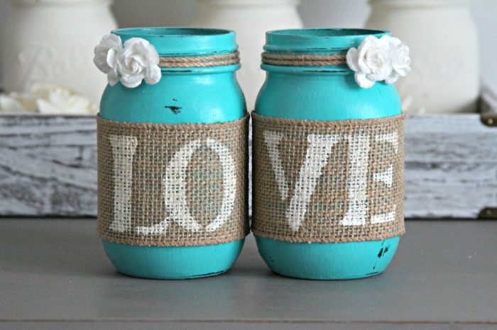 mason jar crafts, two jars painted in turquoise, with small white roses, tied around them with string, decorated with burlap, with the world love written on it