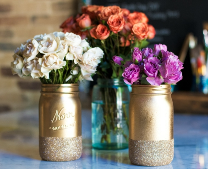 mason jar crafts, two jars spray-painted in gold, with glitter details, containing white and purple flowers, and a clear blue jar, with orange roses, in the background