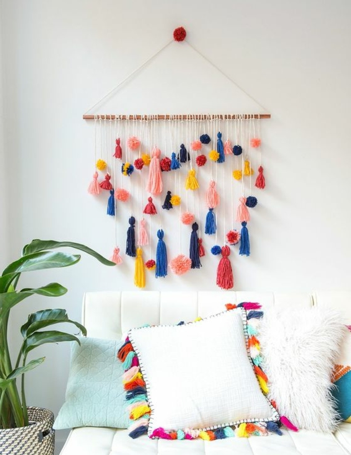 wall decoration made from a piece of wood, adorned with pom-poms, in different shapes and colors, homemade crafts, hanging over a white couch