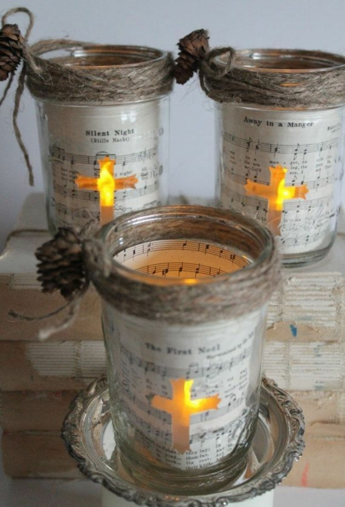 christmas mason jars, three jars decorated with sheet music, and tiny fir cones tied with string, a cross-shaped window reveals, a lit candle in each jar