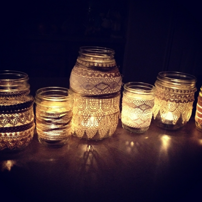 mason jar decorations, several differently sized jars, decorated with lace in different patterns, placed in a dark corner, and lit from within