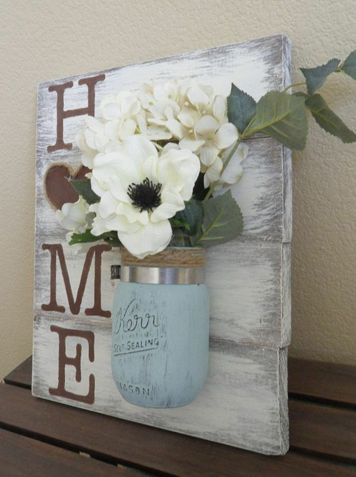 decorating mason jars, off-white wooden board, with the word home written in beige, decorated with a pale blue jar, containing faux white flowers