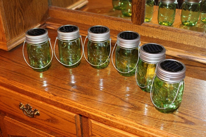 six mason jars, with aluminium lids and wire handles, containing clear green liquid, and placed on a wooden cupboard with mirror