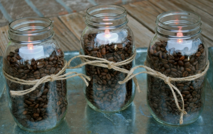decorating mason jars, three jars filled with coffee beans, and decorated with string forming a bow, each containing a lit electric candle