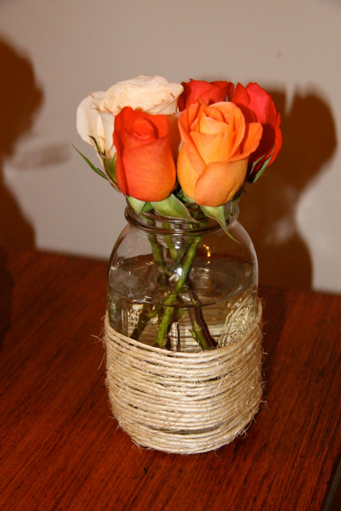 mason jar wrapped around with string, containing four orange roses, and one white, placed on a wooden table