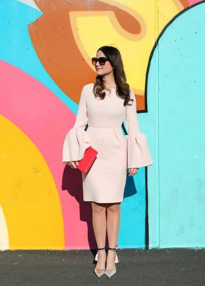 dress attire, brunette woman with wavy hair and sunglasses, wearing knee-length pale peach dress, with long flared sleeves