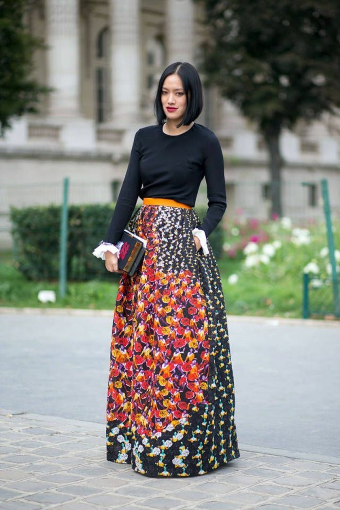 dress attire, black-haired woman with red lipstick, wearing plain black top, tucked into multicolored patterned maki skirt, with yellow belt