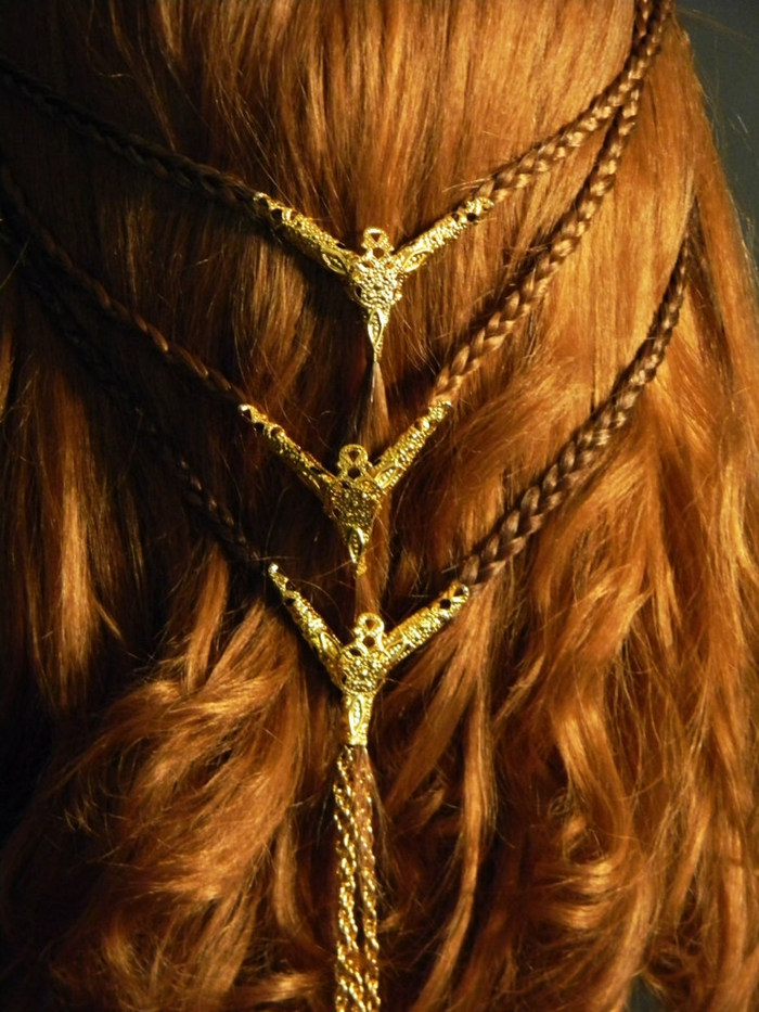 medieval braids, close up of wavy ginger hair, with two rows of small braids, joining in the middle, decorated with gold ornaments